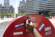 """A participant at the Celebrate Immigrants event placed the flag of the United States with the phrase """"You are Welcome"""" with flags from other countries on the art installation """"I Love Philly"""" on June 4. Photo: Michelle Myers / AL DÍA News"""
