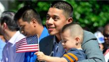 Un padre carga a su hijo durante una ceremonia de naturalización en Greeley, Colorado, el 3 de julio de 2014. (AP Photo/The Greeley Tribune/Joshua Polson)