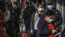 Residents of Brooklyn's Sunset Park wear masks while waiting in line to enter a store in New York on May 5, 2020. Bebeto Matthews/AP