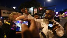 A man shows alleged pictures of the incident to onlookers near a police cordon near Finsbury Park, after a van collision incident in north London, Britain, 19 June 2017. EPA/FACUNDO ARRIZABALAGA
