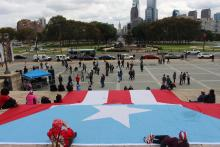 Rally-goers carried a 40 by 60 foot Puerto Rican flag to the Art Museum steps on Oct. 12 to commemorate the over one year that has passed since Hurricane Maria devastated the island. Photo: Emily Neil / AL DÍA News