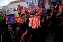 Protestors hold different colored papers showing a drawing of Isabel Cabanillas' face as they take to the street. Photo: Reuters.
