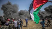 Manifestantes corren para protegerse del gas lacrimógeno lanzado por soldados israelíes durante unas protestas en la frontera de Gaza e Israel el lunes 14 de mayo de 2018.EFE/ Mohammed Saber