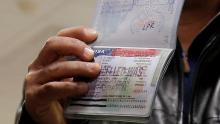 A Yemeni national, who was denied entry into the US in February, 2017 because of a country-based travel ban, shows the cancelled visa in their passport. Credit: Jonathan Ernst/Reuters