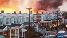 Apologies were finally issued by the city for its role in the MOVE Bombing of 1985.Row houses in Philadelphia burn after policed dropped a bomb on the Move house in May 1985. Photograph: AP
