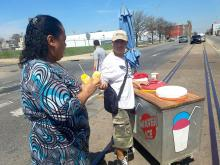 Juanita Pacheco gets a couple of piraguas from Gonzalo Ramirez along American Street. Photo: Peter Fitzpatrick/AL DIA News