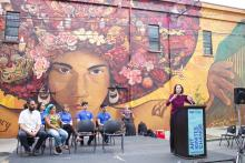 "Jane Golden, executive director of Mural Arts Philadelphia, speaks at the dedication ceremony of the ""Sanctuary City, Sanctuary Neighborhood"" mural on the wall of the Providence Center at Fifth and Huntingdon streets in Fairhill. Photo: Emily Neil / AL DÍA News"