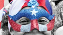 A woman wears a mask with the Puerto Rican flag at the parade.