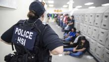 A US Immigration and Customs Enforcement officer walks past detained immigrants during a raid at a Mississippi chicken processing plant. US Department of Homeland Security/Immigration and Customs Enforcement.