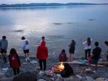 A group of teenagers skip stones across the water at sunset May 17, 2020 on Lake Champlain in Charlotte, Vermont. Photo: Robert Nickelsberg / Getty Images.