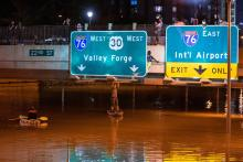 A kayaker poses for a photo under a highway sign when paddling down a portion of Interstate 676 after flooding from heavy rains from hurricane Ida in Philadelphia, Pennsylvania on September 2, 2021. Photo: Branden Eastwood/AFP via Getty Images.