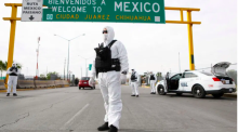 Chihuahua State Police members, wearing protective suits, take part in an information and prevention campaign against the coronavirus -COVID-19- pandemic, at the Cordoba-De las Americas International Bridge in Ciudad Juarez, Chihuahua, Mexico, on March 29, 2020. Photo: Henrika Martinez/Getty Images.