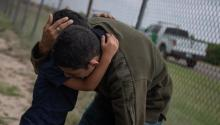 Stock Photo: A four-year-old child cries in the arms of a family member while border patrol agents apprehended him and others after illegally crossing the Mexican border near McAllen, Texas, U.S., May 2, 2018. REUTERS/Adrees Latif.