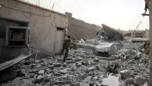 Member of the Syrian Democratic Force walks in the middle of rubble in Raqqa (Rodi Said / Reuters)