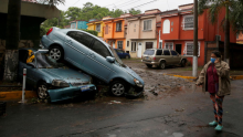 A woman walk in front of damaged cars during floods caused by Tropical Storm Amanda, in San Salvador, El Salvador May 31, 2020. © REUTERS/Jose Cabezas TPX