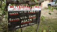 A handmade sign to deter trespassers hangs in the front yard of Fernando Rivera Jr.'s house in Brownsville, Texas, September 2, 2014. REUTERS/Rick Wilking