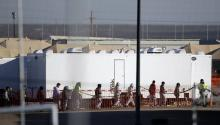 In this Dec. 13, 2018 file photo, migrant teens walk in a line through the Tornillo detention camp in Tornillo, Texas. Andres Leighton—AP