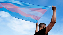 Someone raising the trans flag. Photo by ISTOCK.