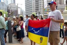Members of Casa de Venezuela Myrteny Metzger (left) and Nicolas Di Giulo (right) raise the Venezuelan flagduring an event at City Hall. Greta Anderson / AL DÍA News