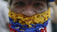 CARACAS, VENEZUELA - JULY 05: A Venezuelan wears ribbons of Venezuelan colors to cover her mouth as people gather at PNUD for a demonstration called by opposition leader Juan Guaido during the 208th anniversary of the Venezuelan Independence declaration on July 5, 2019 in Caracas, Venezuela. (Photo by Matias Delacroix/Getty Images)