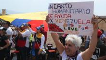 Una mujer sostiene un cartel durante el concierto Venezuela Aid Live este viernes, en el puente fronterizo de Tienditas, en Cúcuta (Colombia). EFE/Mauricio Dueñas Castañeda