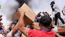 People try to take part of the humanitarian aid that is a truck that was burned, this Saturday, in Ureña (Venezuela). Two trucks with humanitarian aid requested by the opposition were burned by the Bolivarian National Police on the Venezuelan side of the Francisco de Paula Santander bridge, which connects the country with Colombia, deputy Gaby Arellano denounced. EFE/Deibison Torrado