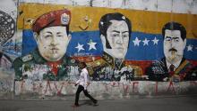 CARACAS, VENEZUELA - JANUARY 30: A man walks past a mural depicting Venezuela's late President Hugo Chávez, Latin American independence hero Simon Bolivar and Venezuela's President Nicolás Maduro on January 30, 2019 in Caracas, Venezuela. (Photo by Marco Bello/Getty Images)