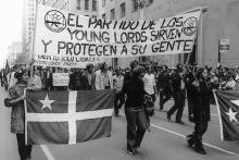 "Young Lords members march with a sign that reads, ""The Party of the Young Lords serves and protects your people."" Iris Morales. ¡Palante, Siempre Palante!, 1996. Film."